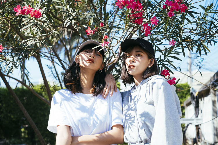 Portrait of friends standing against flowering plants