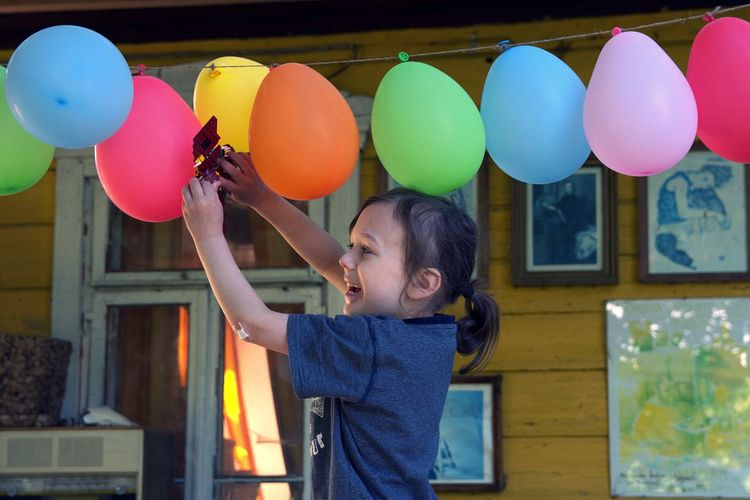 Side view of smiling girl playing with colorful balloons at home