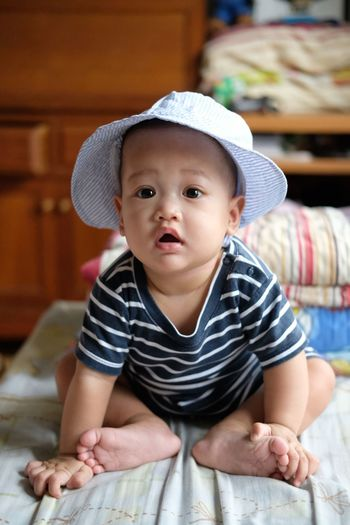 Portrait of cute baby boy in hat sitting on bed at home
