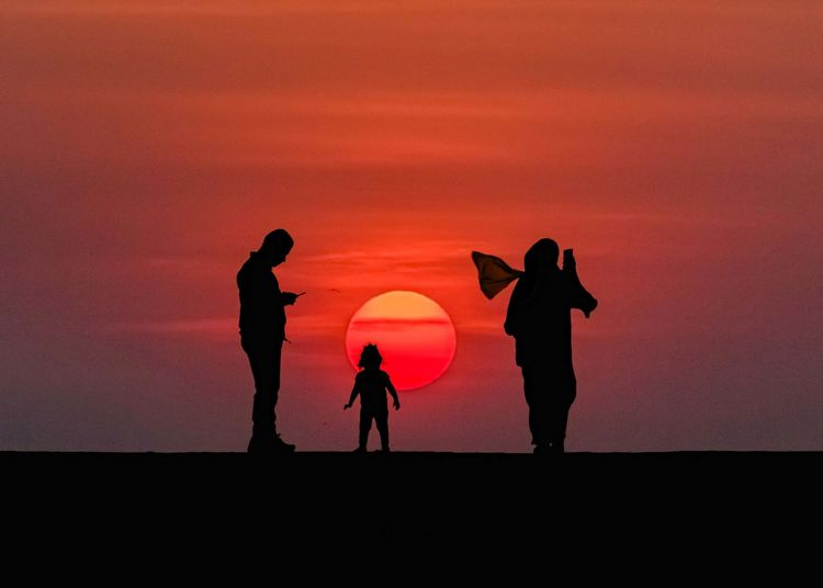 Silhouette family against orange sky during sunset