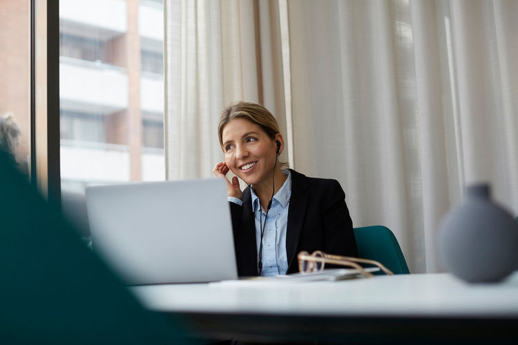 Portrait of smiling woman using smart phone while sitting on table