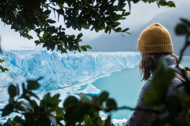 Looking at Glacier Perito Moreno, Argentina Ice Laguna Argentina Beauty In Nature Clothing Day Glacier Hat Headshot Leisure Activity Looking At View Nature One Person Outdoors Perito Moreno Real People Rear View Tree Water Winter Women Yellow Hat