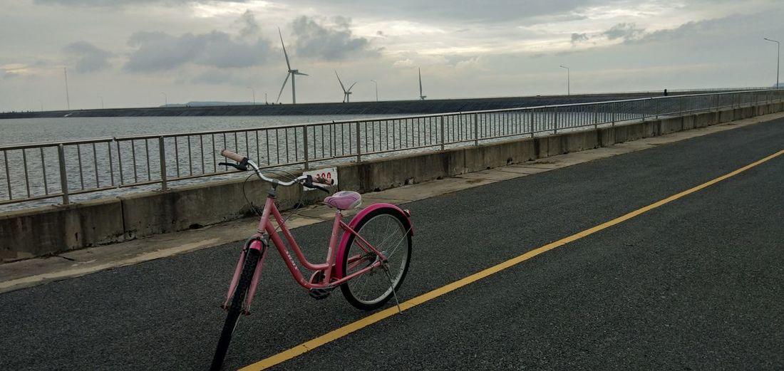 Bicycle on bridge against sky