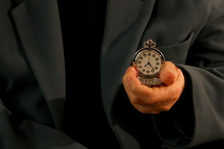 Midsection Of Man Wearing Suit Holding Pocket Watch