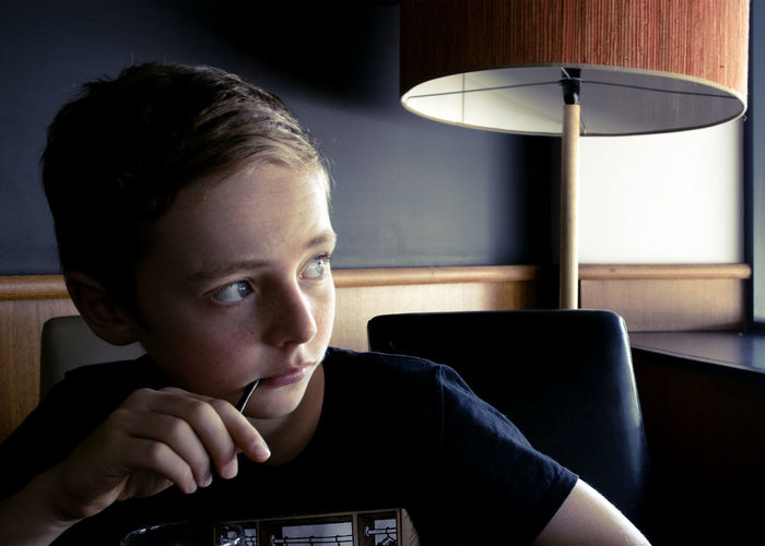 Close-up of boy looking away while sitting at home