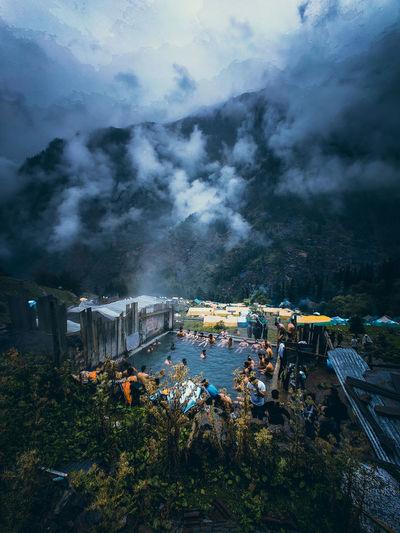 People enjoying natural hot water spring in kheerganga, kasol, himachal pradesh, india