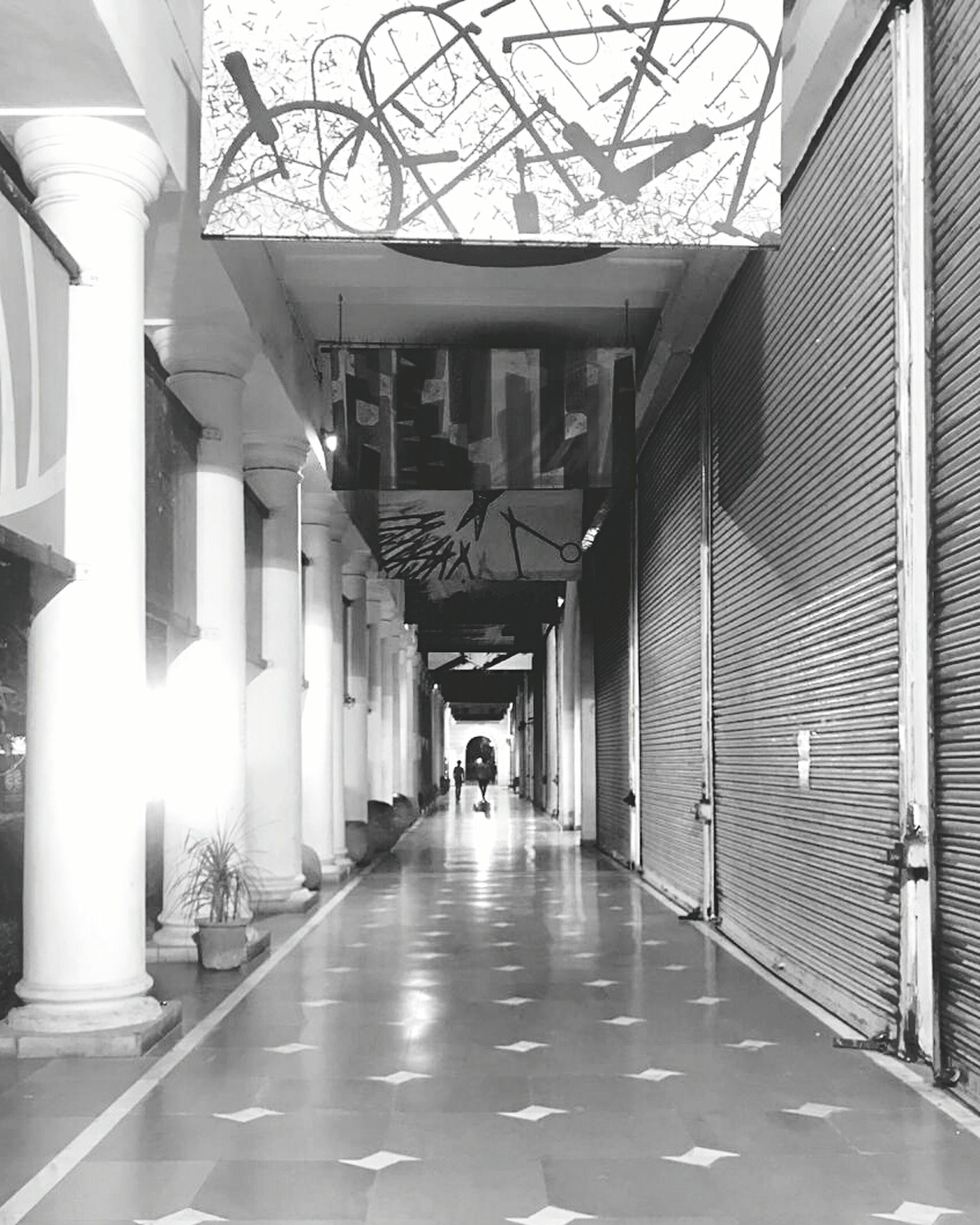 architecture, built structure, building, indoors, ceiling, the way forward, architectural column, direction, arcade, corridor, illuminated, flooring, real people, day, incidental people, empty, diminishing perspective, in a row, arch, footpath, tiled floor