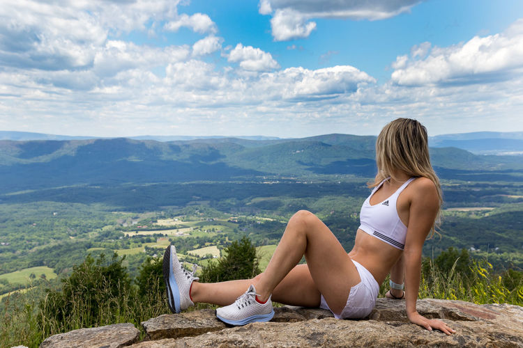 Woman sitting on mountain looking at view