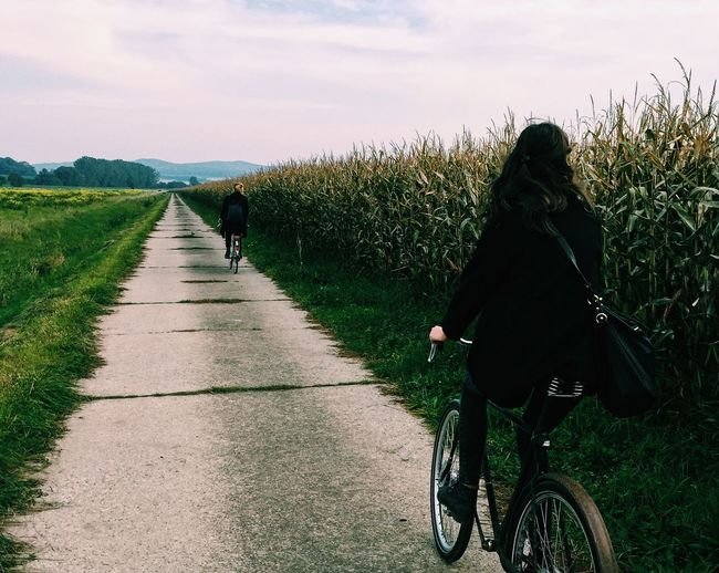 Full Length Rear View Of Friend Riding Bicycles On Road By Agricultural Field Against Sky