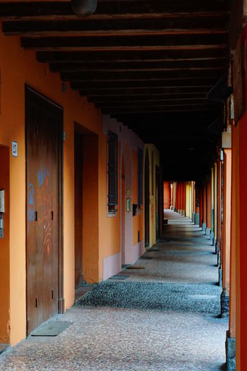 Colorful Pillars Colourful Portico Corridor Diminishing Perspective I Portici Di Bologna In A Row In The Streets Of Bologna No People No Photoshop, No Filter Orange And Red Colour The Way Forward Wooden Ceiling Wooden Doors