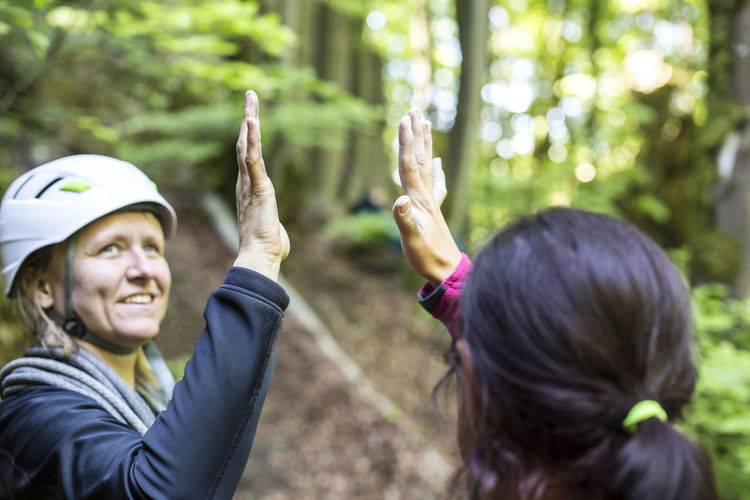 Close-up of friends high-fiving in forest
