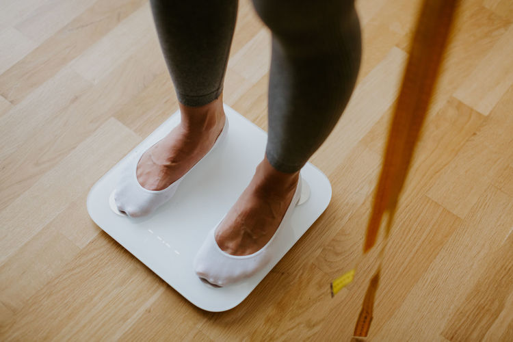 Low section of person standing on wooden floor at home
