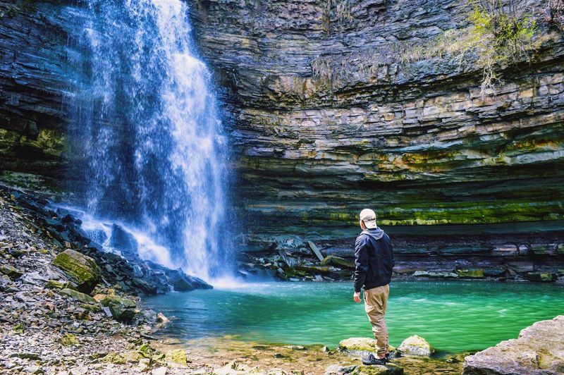 Man standing in front of waterfall