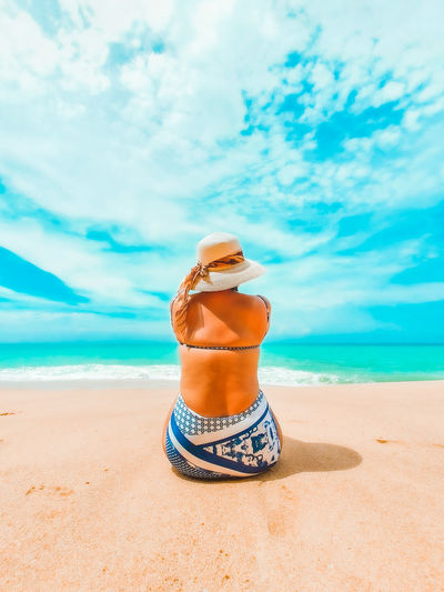 Woman wearing hat sit on the sandy beach against sky