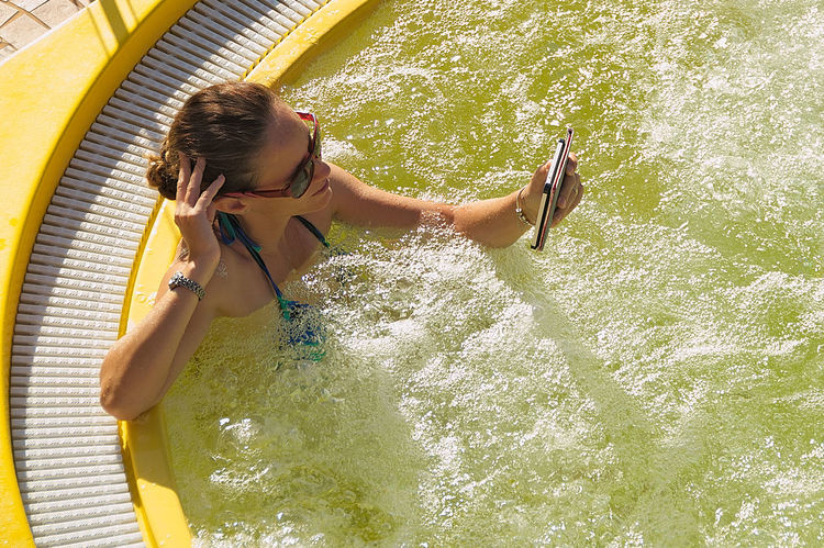 Young woman relaxes by reading in the pool Adult Adults Only Hydromassage Leisure Activity One Person One Woman Only One Young Woman Only Only Women Outdoors People Reading Reading & Relaxing Relaxation Summer Sunlight Swimming Pool Tecnology Vacations Water Women Women Around The World Yellow Young Adult Young Women