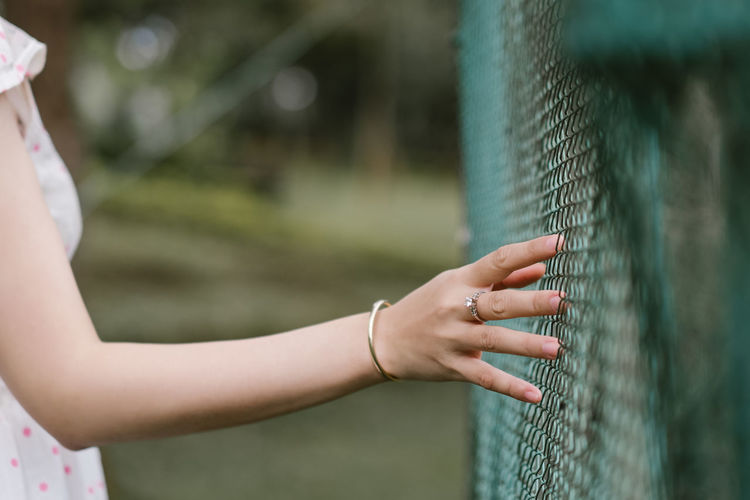 Close-Up Of Woman Touching Fence