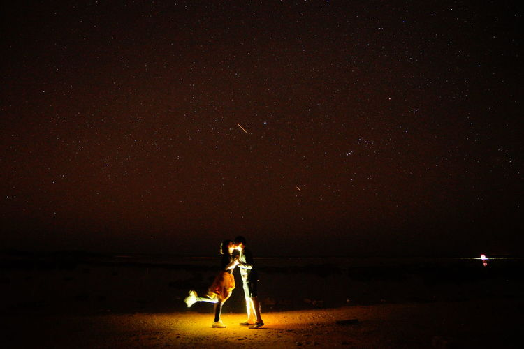 Side View Of Couple Kissing At Beach Against Star Field At Night