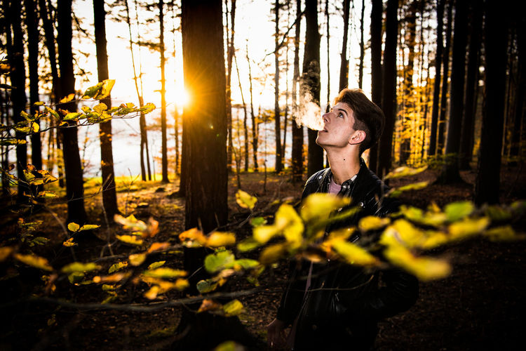 Man exhaling smoke in forest