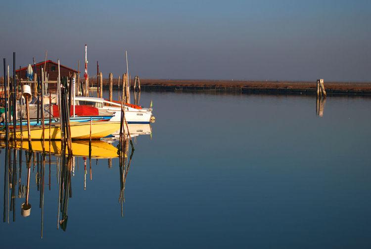 Boats moored in calm lake