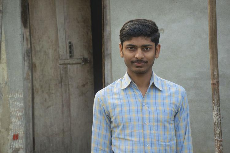 Portrait of teenage boy of indian village standing in front of the house doorway