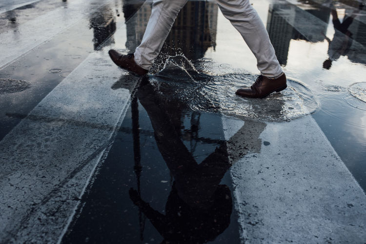 Low section of man walking on wet street