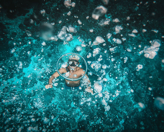 High angle view of man free diving making water rings swimming in sea