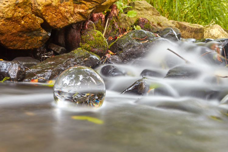 Crystal ball in stream at forest