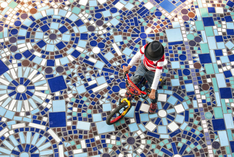 High angle view of boy cycling on mosaic walkway