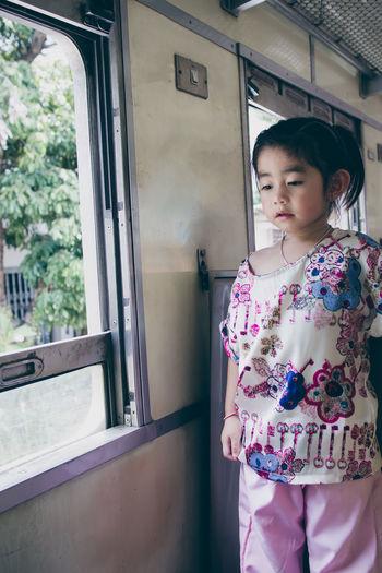 Full length of cute girl standing against window