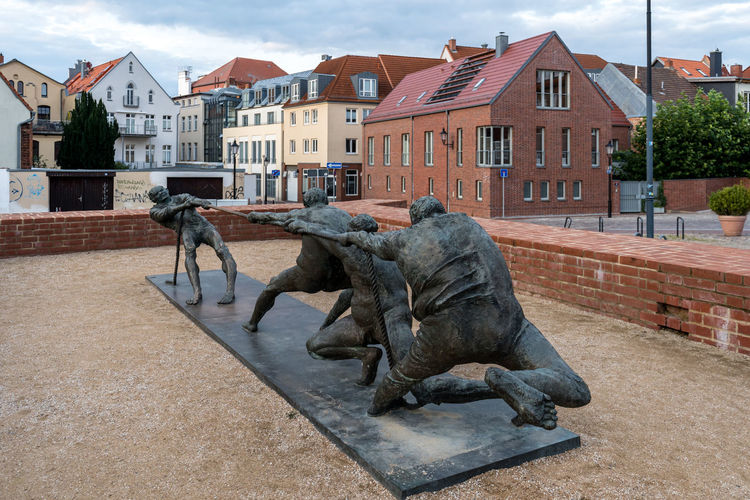 Horse statue by buildings in city against sky