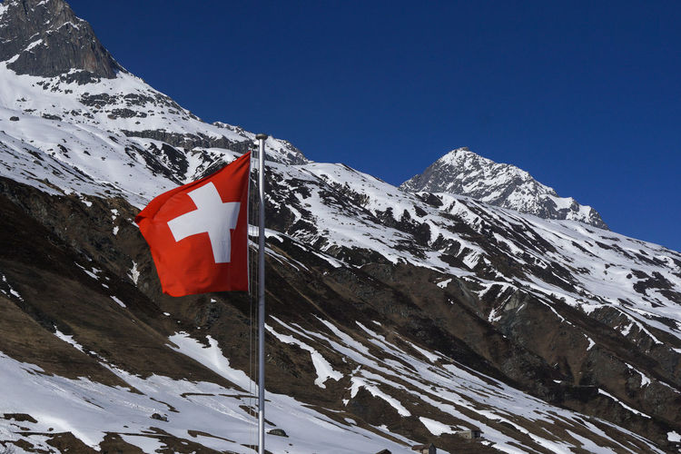 Scenic view of swiss flag in front of snowcapped mountains against clear sky