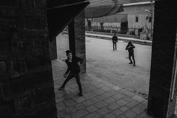 Men walking on cobblestone street