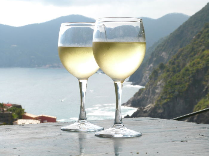 Close-up of wineglasses on table against mountains