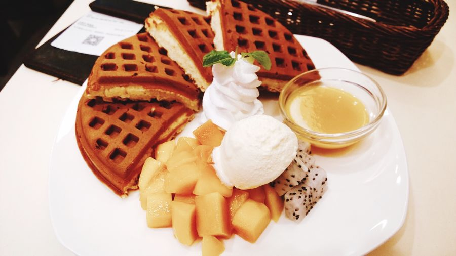 Close-Up Of Waffles With Cream And Fruits Served In Plate