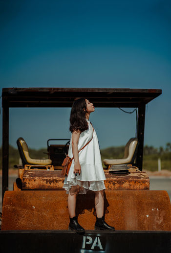 Full length of young woman standing on rusty vehicle against clear sky