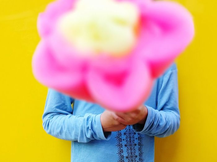 Man Holding Cotton Candy While Standing Against Yellow Wall