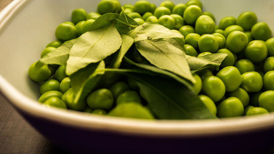 Close-Up Of Green Peas And Leaves In Bowl On Table