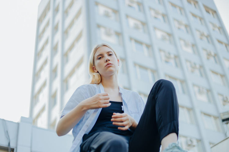 Low angle view of young woman sitting against building