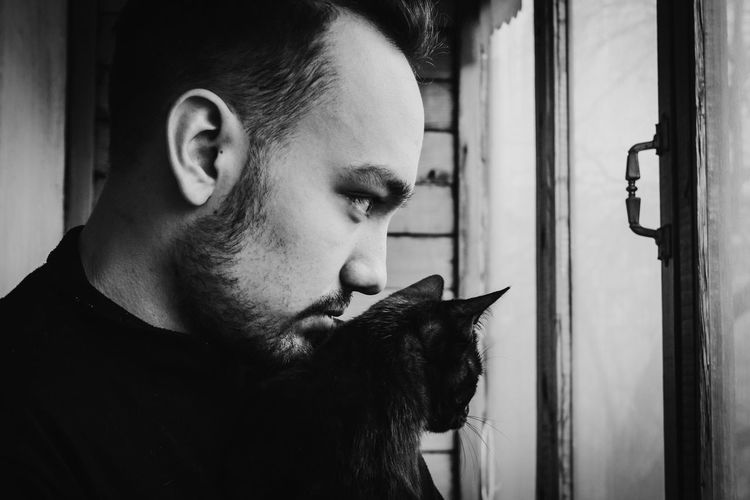 Man With Cat Looking Through Window