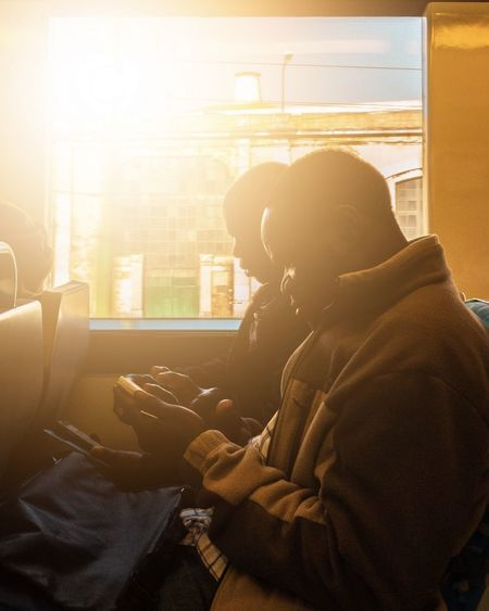 Side view of woman using mobile phone while sitting on window