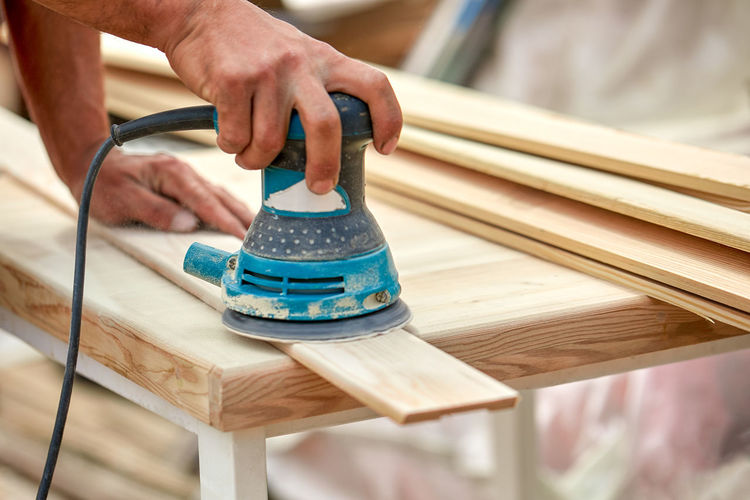 Cropped hands of carpenter working in workshop