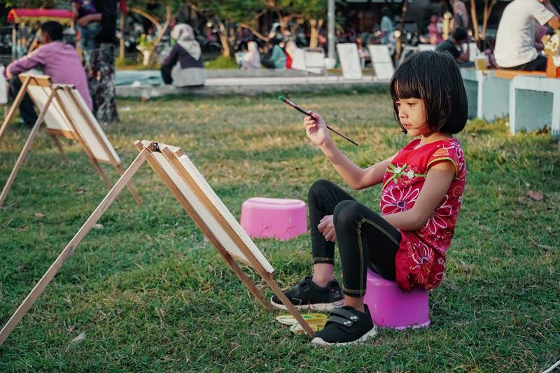 Side view of cute girl painting in park