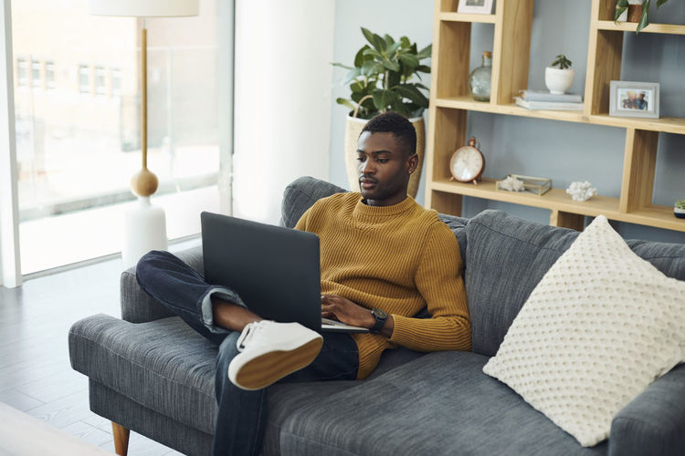Man using mobile phone while sitting on sofa at home