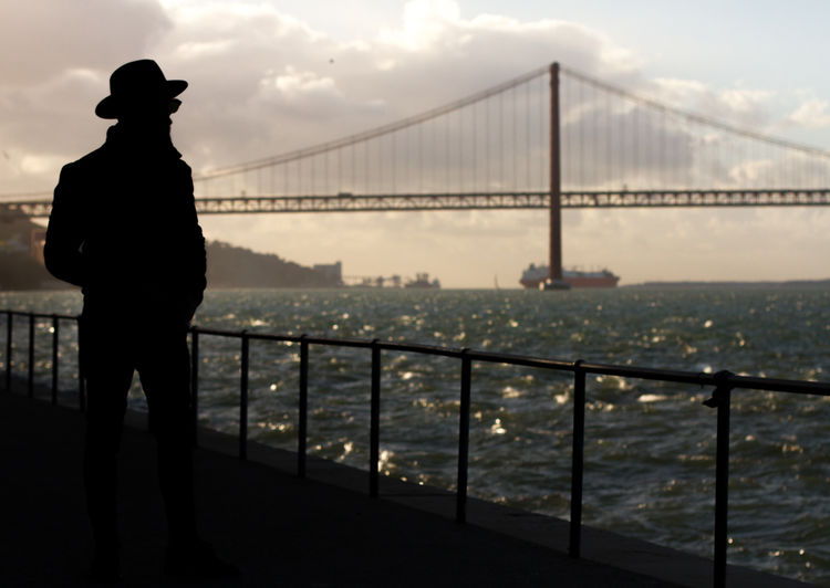 Silhouette man standing by suspension bridge in city