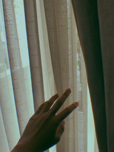 Cropped hand of woman holding curtain at home