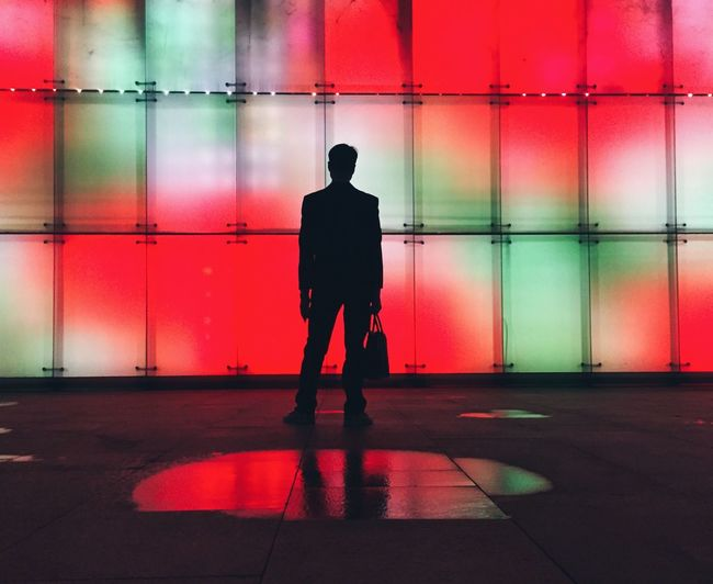 Silhouette man standing against illuminated wall at night