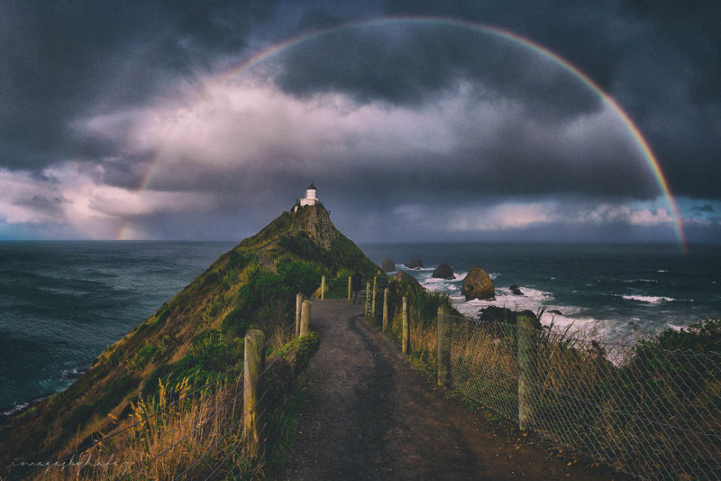 Nugget Point Lighthouse, framed. This was my third time to this famous lighthouse in the Otago Region, New Zealand and it was the first time I'd managed to capture a rainbow framing the lighthouse. Rain was about to fall, and luckily I'd turn around to see the lighthouse one last time before heading to the carpark. Shot with my Sony RX100 IV, handheld. Post processed later by combining 5 photos into a panorama. Beauty In Nature Cloud - Sky Day EyeEm Best Edits EyeEm Best Shots EyeEm Nature Lover Horizon Over Water Idyllic Lighthouse Nature No People Nugget Point Lighthouse Outdoors Rainbow Scenics Sea Sky Storm Storm Cloud Tranquil Scene Tranquility Travel Destinations Water
