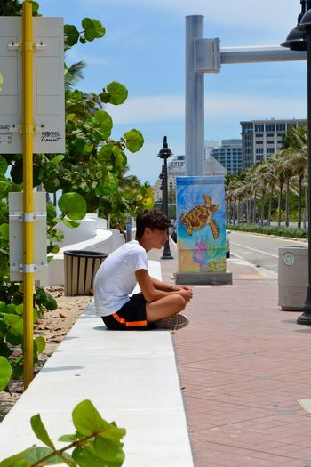 Side view of young man sitting on footpath