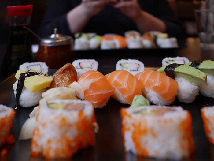 Close-up of sushi against person sitting at table