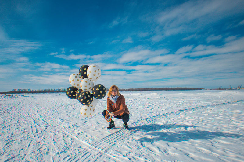 Portrait of woman holding balloons on snow covered land